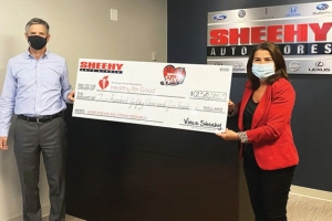 Vince Sheehy, President of Sheehy Auto Stores, presents a check to Soula Antoniou, Executive Director of the American Heart Association.